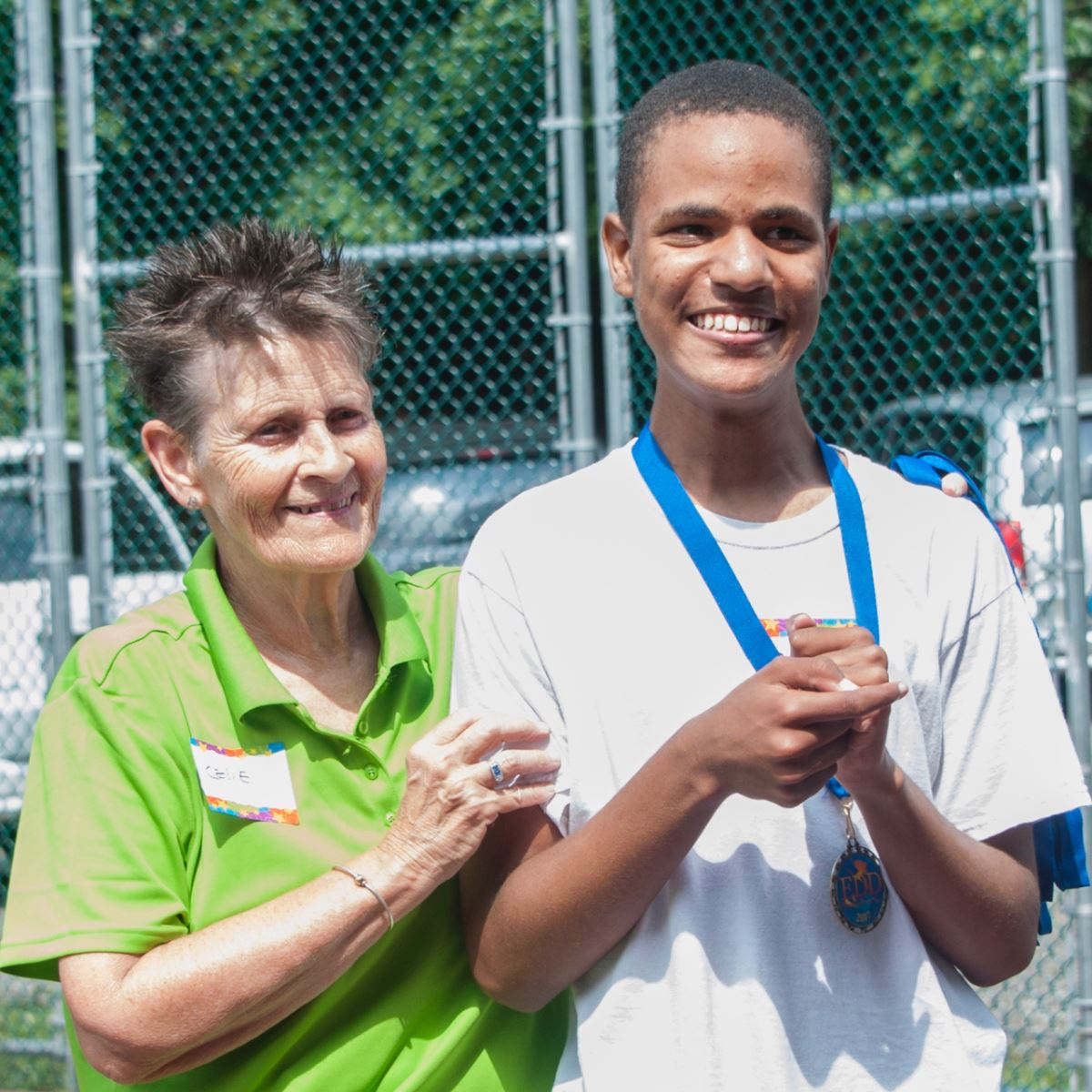 EDD Volunteer and Pickleball player smiles after receiving his medal