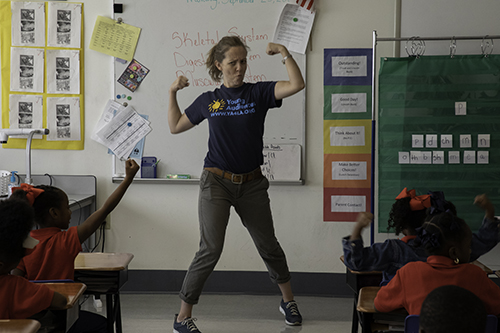Teaching artist stands in front of the classroom holding up her muscles in an exaggerated stance.